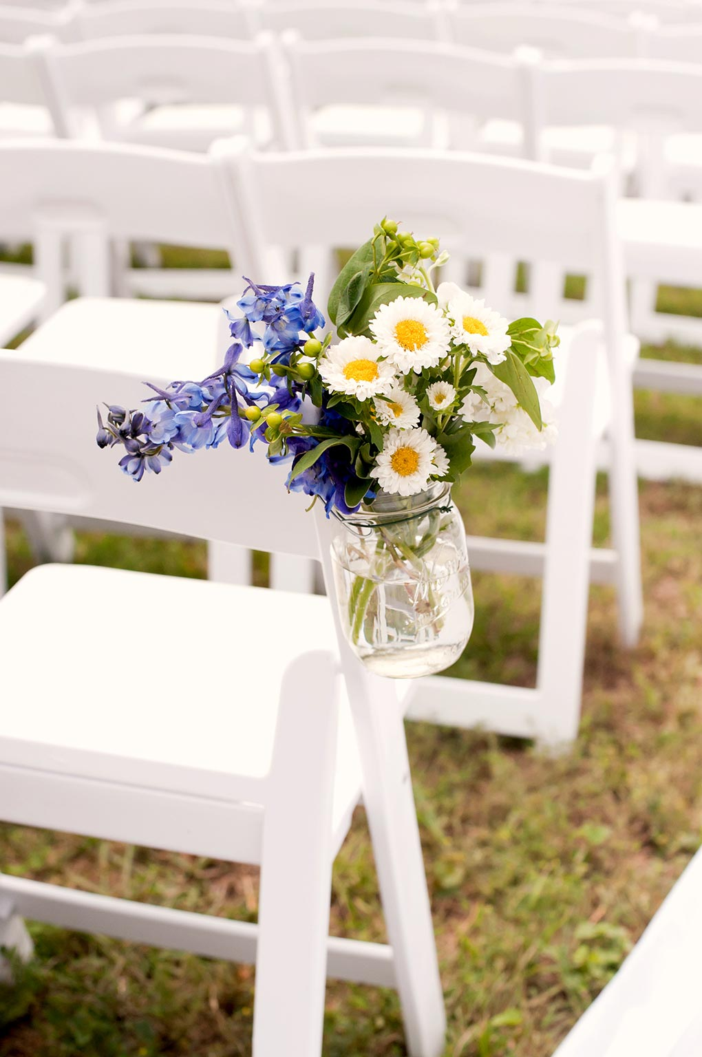 Texas Ranch Wedding white garden chairs and mason jar floral arrangement