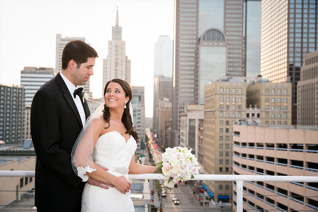 Bride and groom wedding day portrait overlooking downtown Dallas at The Room on Main