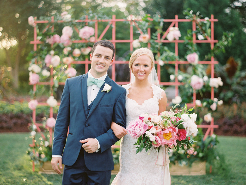 Bride and groom take a wedding day portrait in front of a pink floral lattice at The Dallas Arboretum