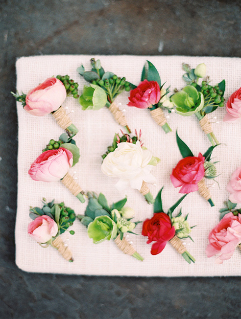 Pink and peach ranunculus wedding groomsmen boutonnieres with twine wraps
