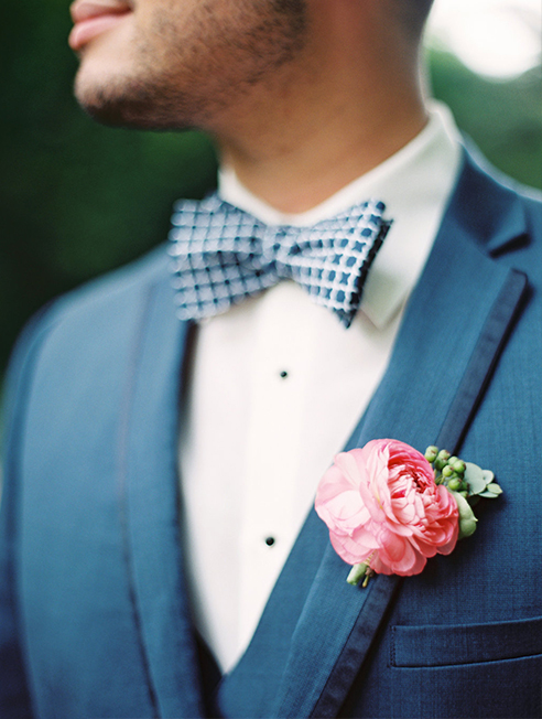 Navy wedding groomsman suit and bow tie with pink ranunculus boutonniere