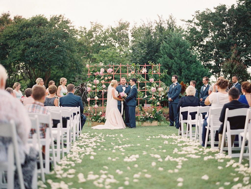 Bride and groom in front of floral lattice altar backdrop at wedding ceremony at The Dallas Arboretum