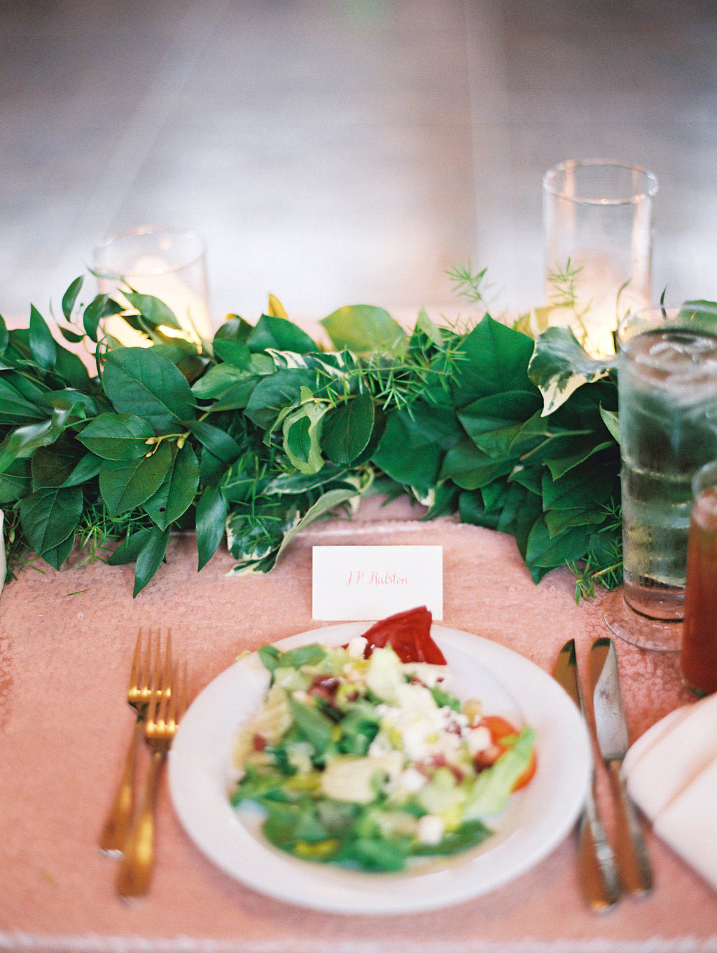 Green garland table runner and wedding place setting with salad