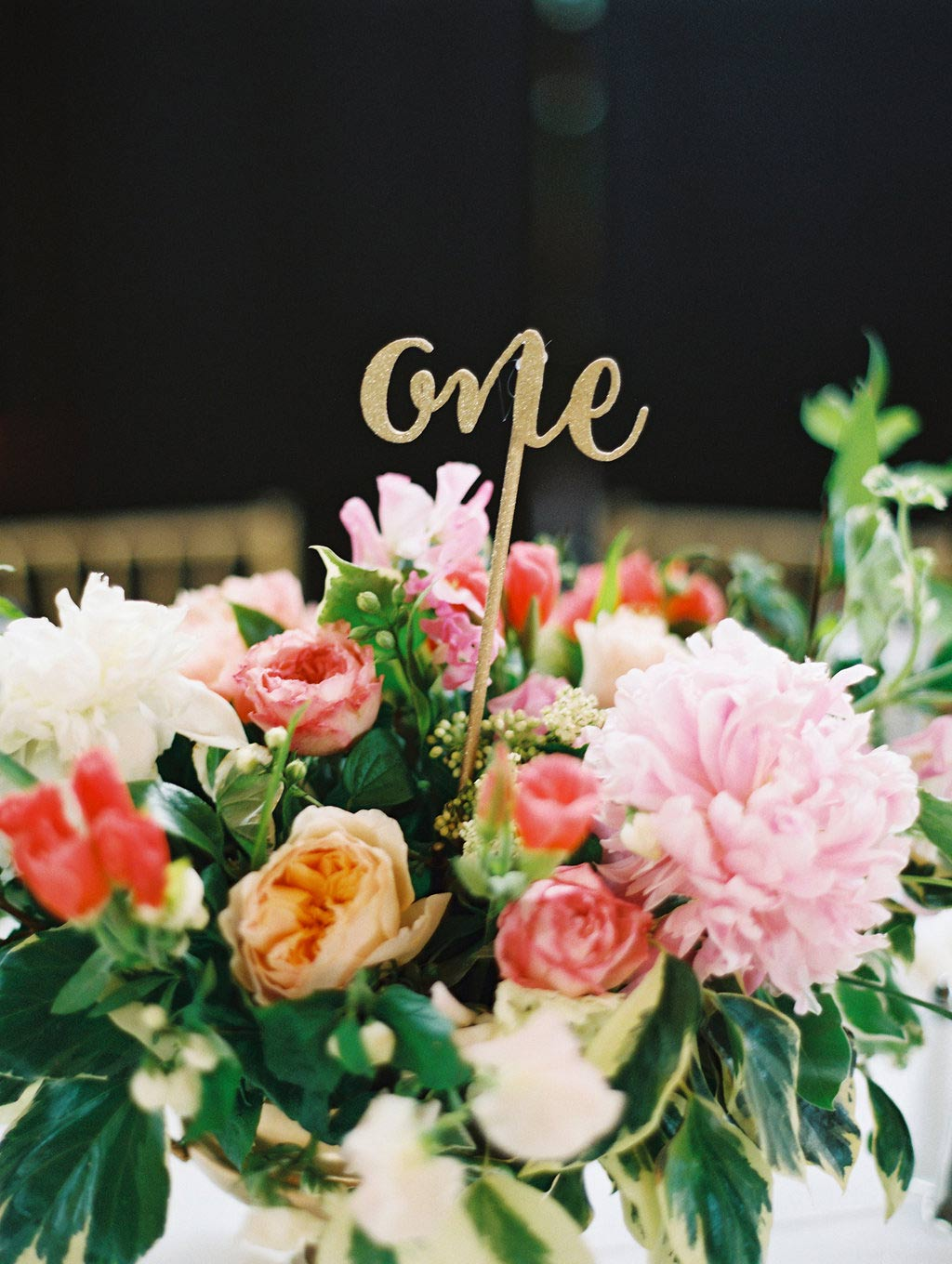 Low floral wedding centerpiece with gold script table number dowel