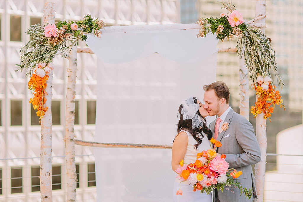 Bride and groom take a wedding day portrait on a rooftop outside in front of downtown Dallas buildings at The Venue at 400 North Ervay