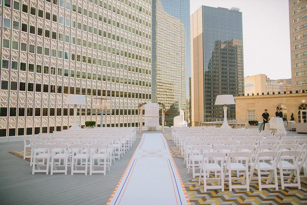 Wedding ceremony setup with custom aisle runner and chuppah on a downtown Dallas rooftop at The Venue at 400 North Ervay