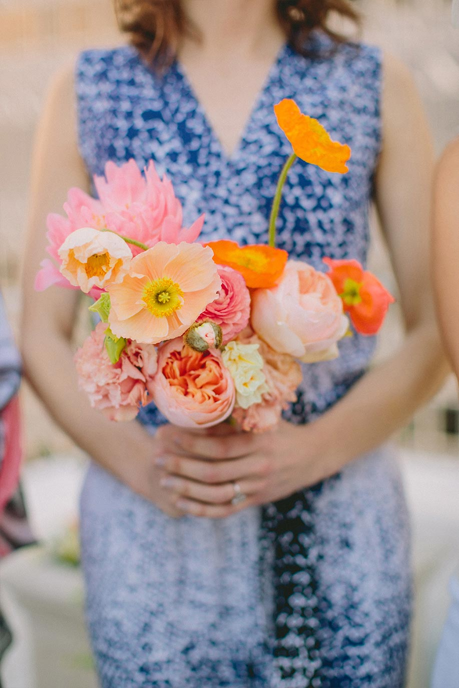 Bridesmaid with pink and orange bouquet and mix and match dress