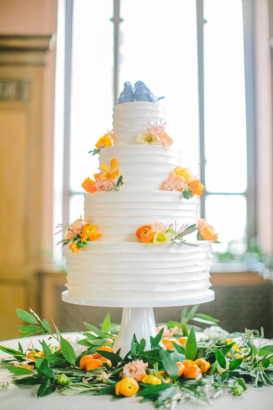 Buttercream wedding cake with orange and yellow flowers and blue and white porcelain topper