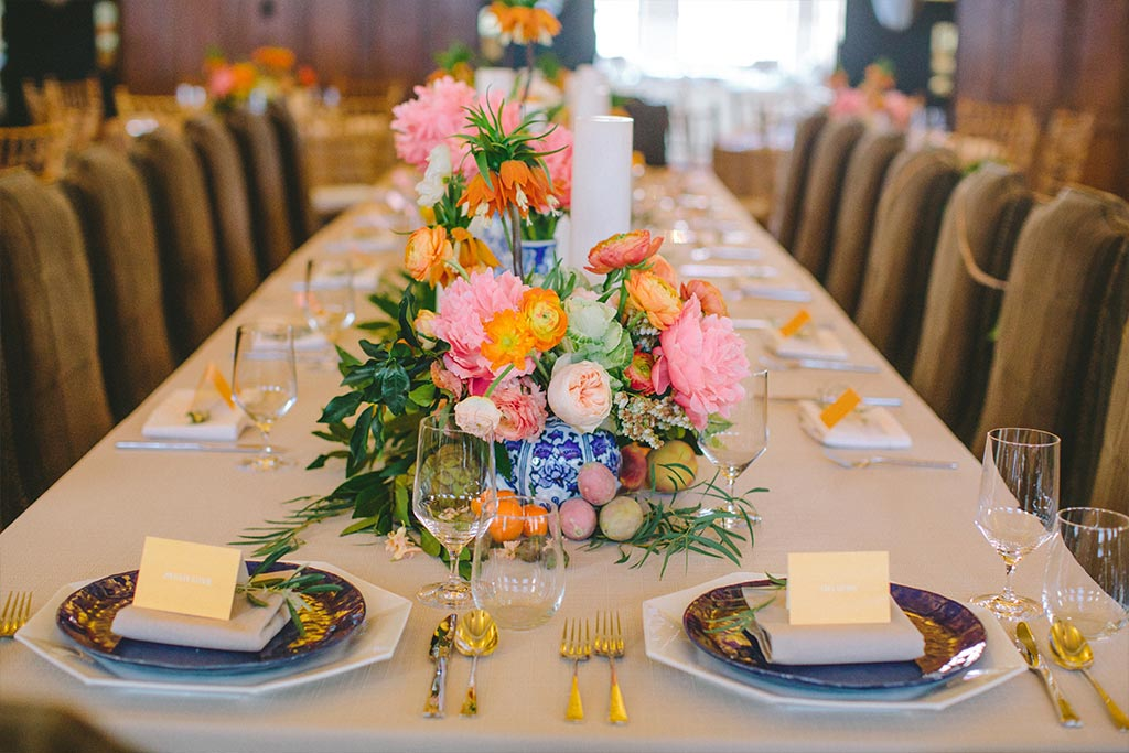 Wedding place settings with pink, orange, and blue details