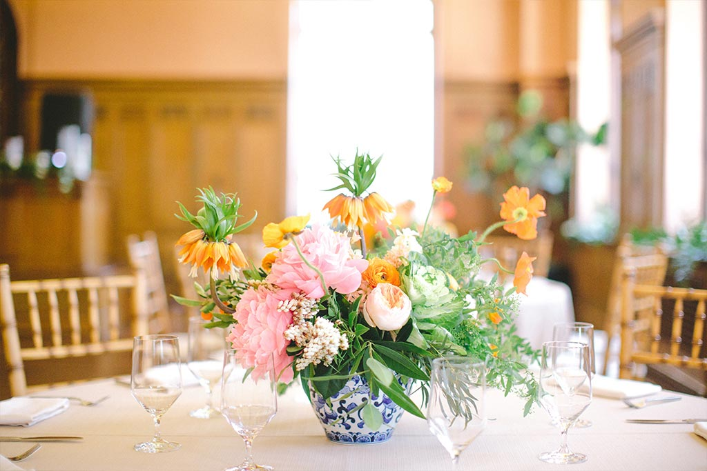 Pink and orange floral wedding centerpiece in blue and white porcelain vase