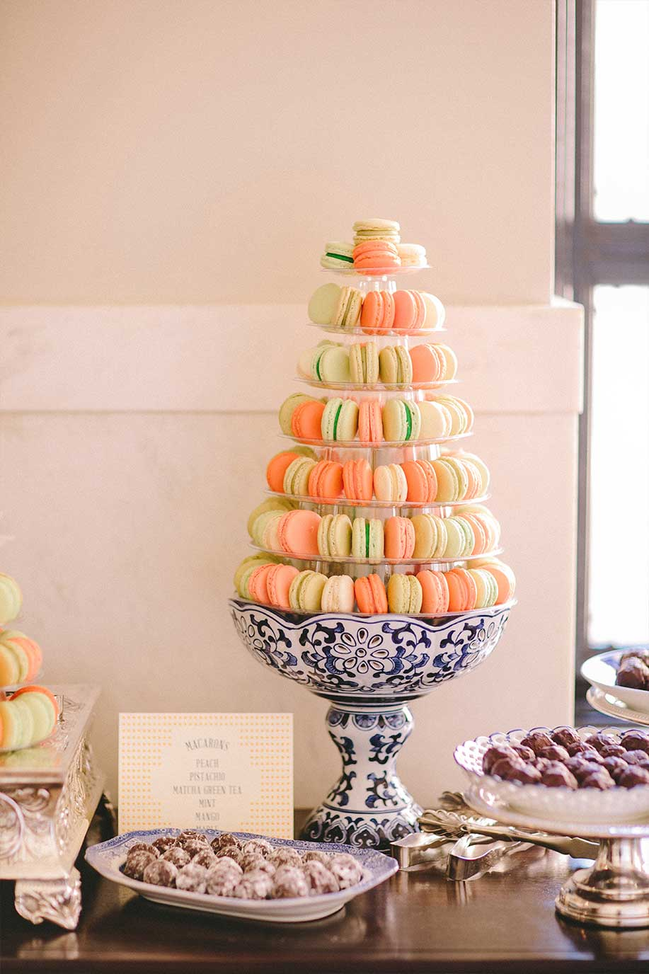 Wedding dessert table with macaroons and chocolate truffles on blue and white porcelain