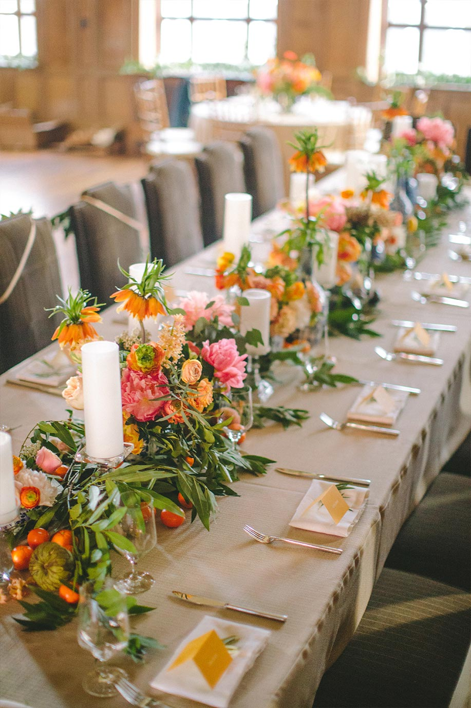 Long wedding head table with orange place cards, greenery and fruit garland