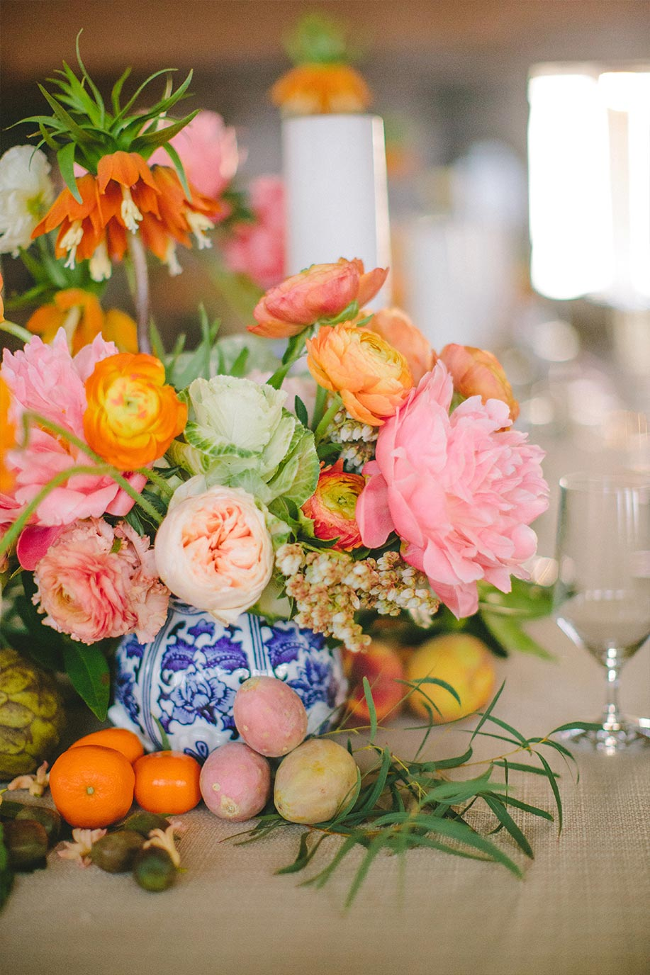Pink and orange floral wedding centerpiece in blue and white porcelain vase with greenery and fruit