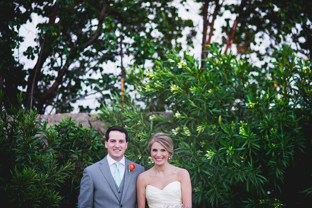Bride and groom take a wedding day portrait in front of greenery at Hickory Street Annex in Dallas