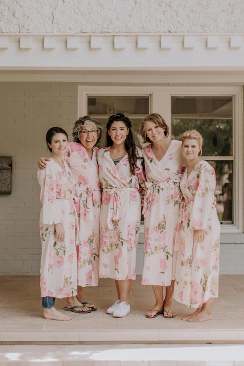 Bride and bridesmaids getting ready for wedding day with pink floral silk robes