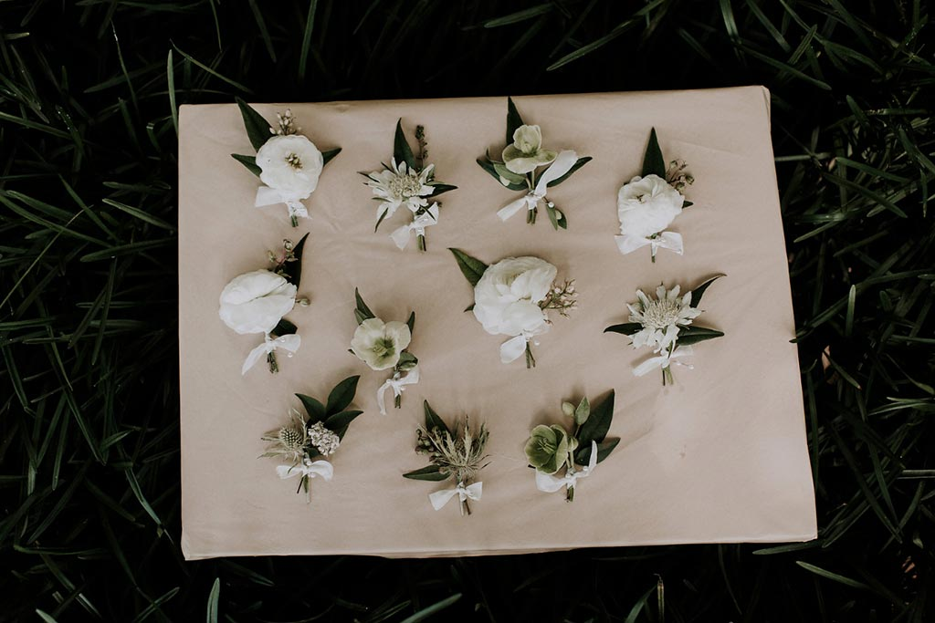White ranunculus boutonniere for groomsmen