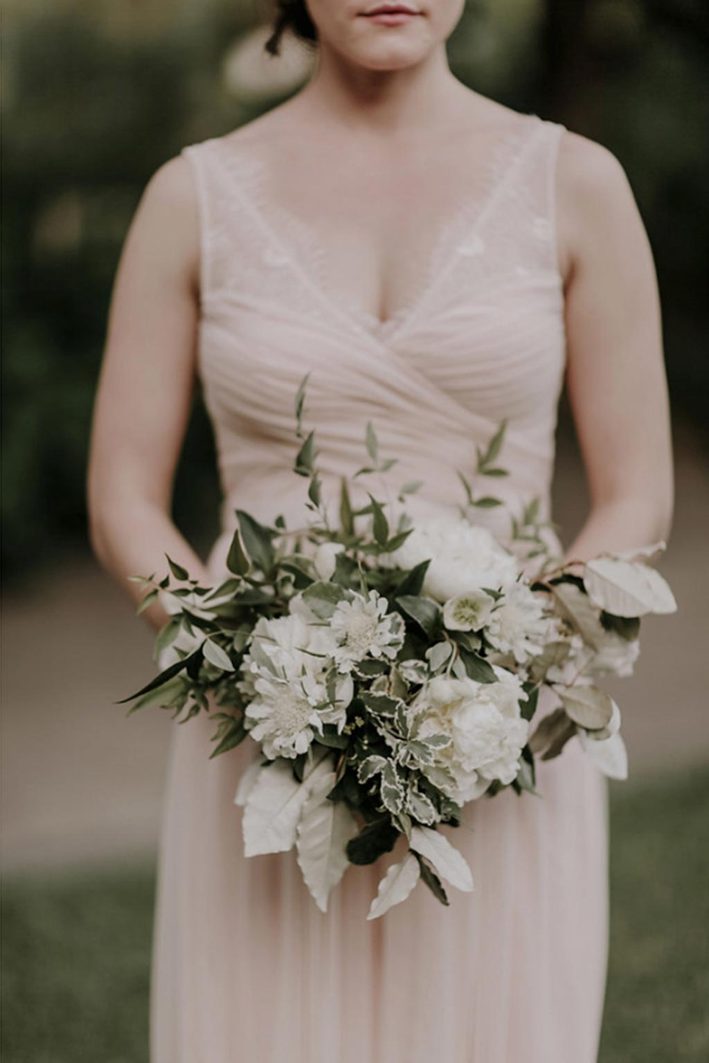 Bridesmaid with peach sleeveless gown and white and green natural bouquet