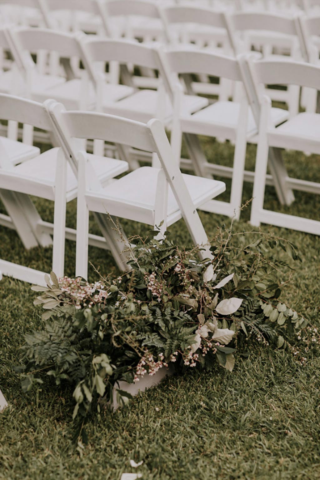 Natural green and white wedding aisle floral arrangement with white garden chairs