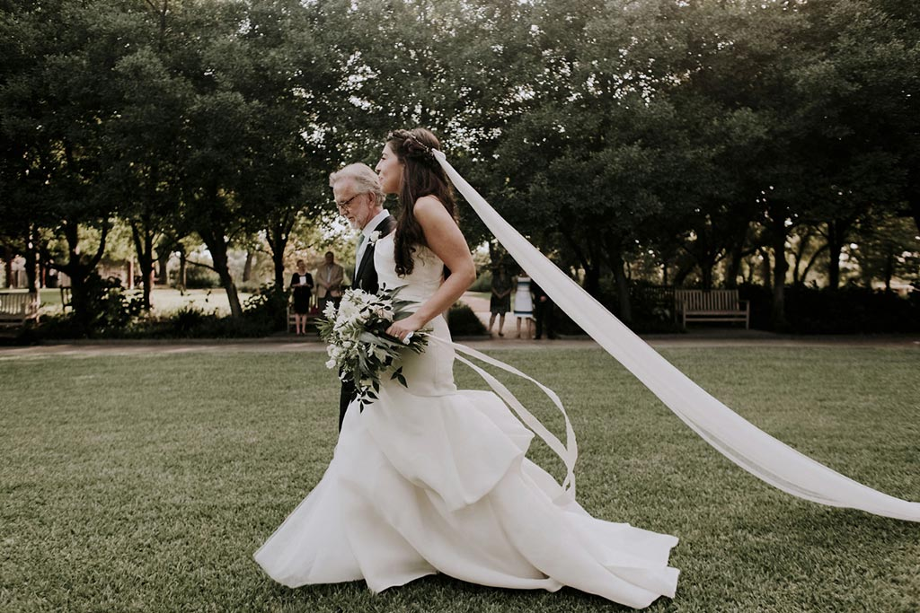 Father walking bride down the aisle with cathedral length long veil and Madison by Monique Lhuillier gown
