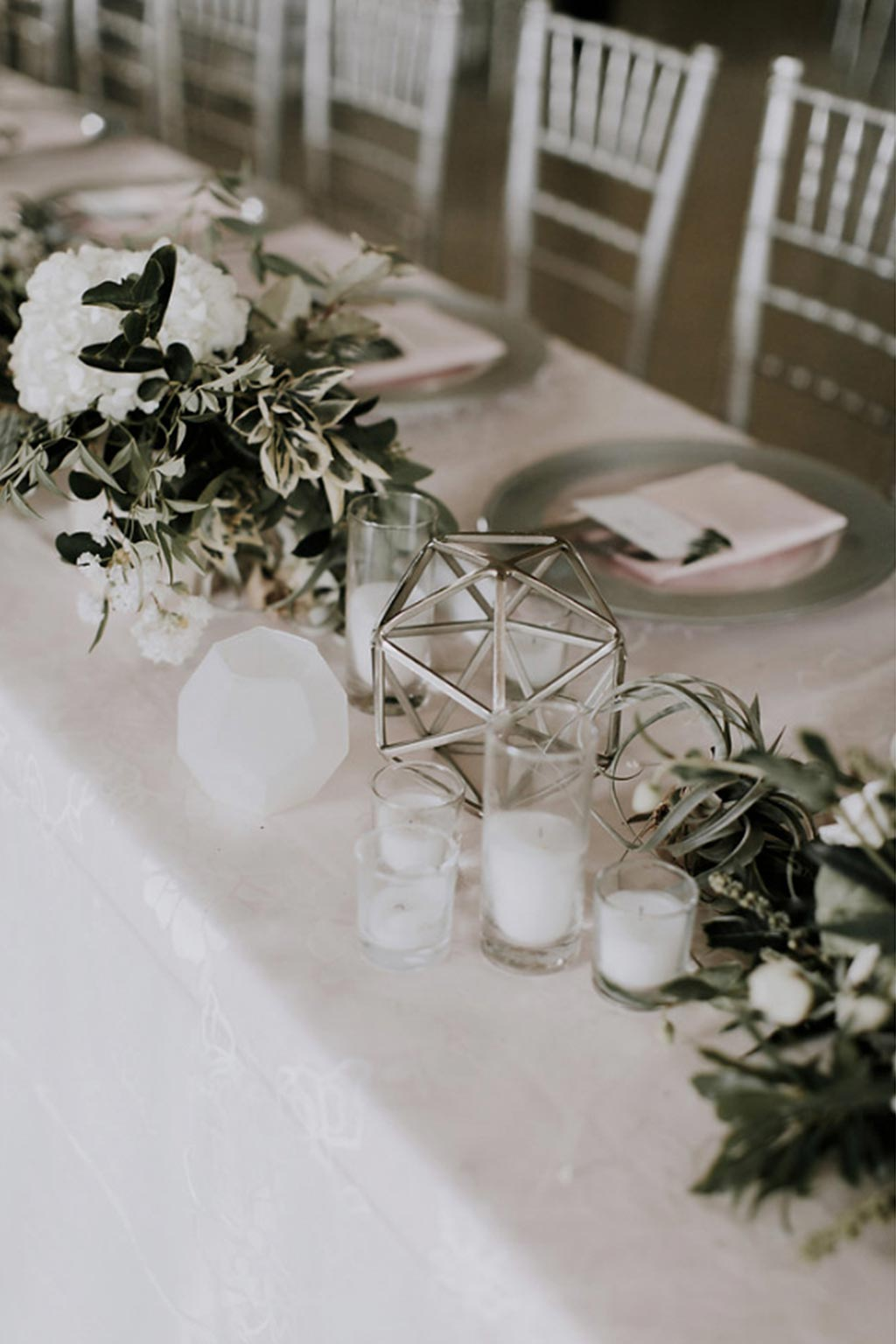Long head table with silver chiavari chairs, faceted terrarium with green and white organic garland wedding centerpiece, and silver and glass, pink napkin placesetting with menu and fern leaf