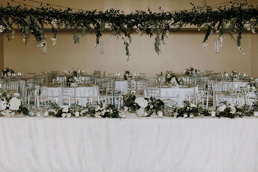 Long wedding head table with hanging organic greenery installation at Texas Discovery Gardens in Dallas