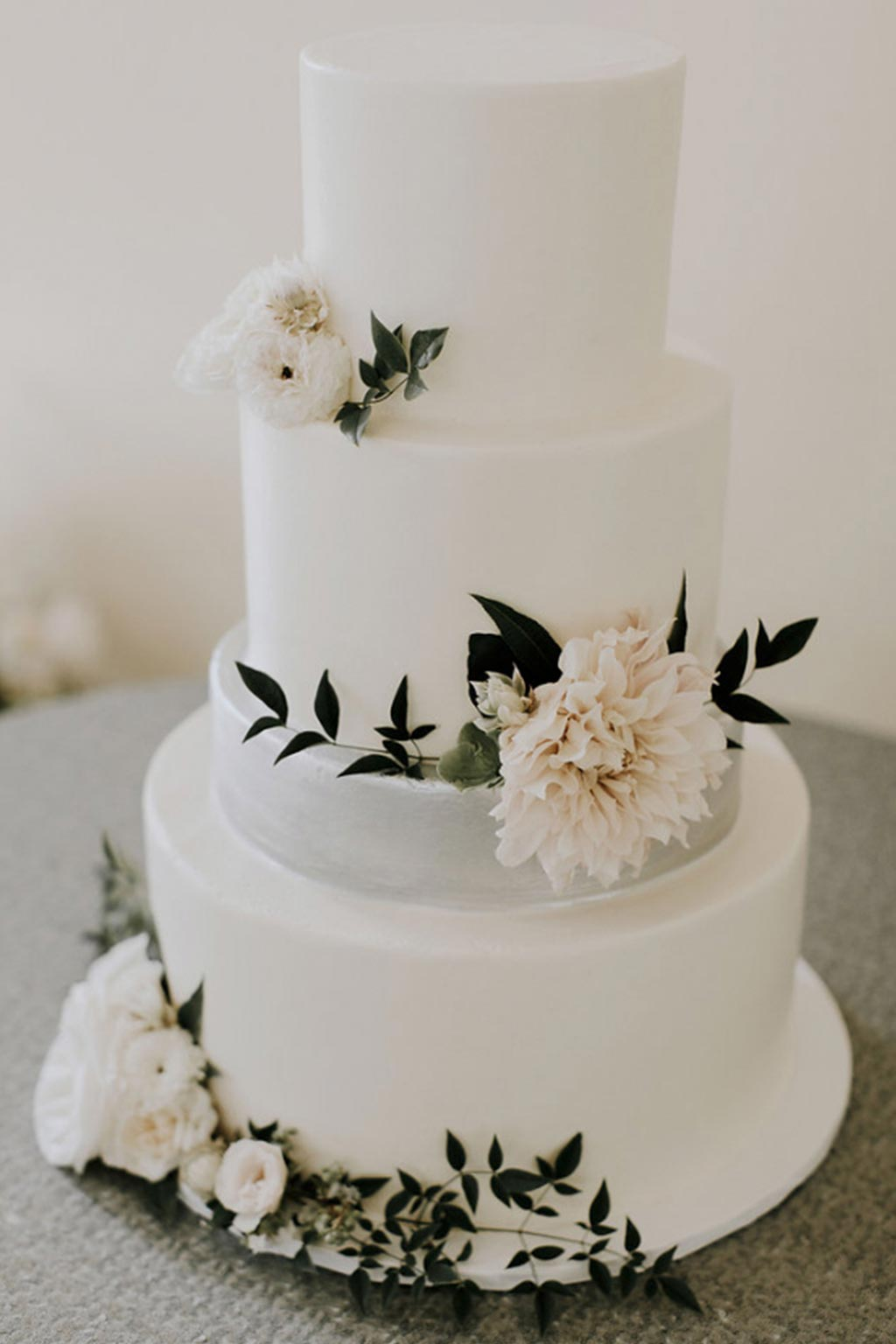 Smooth buttercream wedding cake with a silver metallic layer and frech blooms