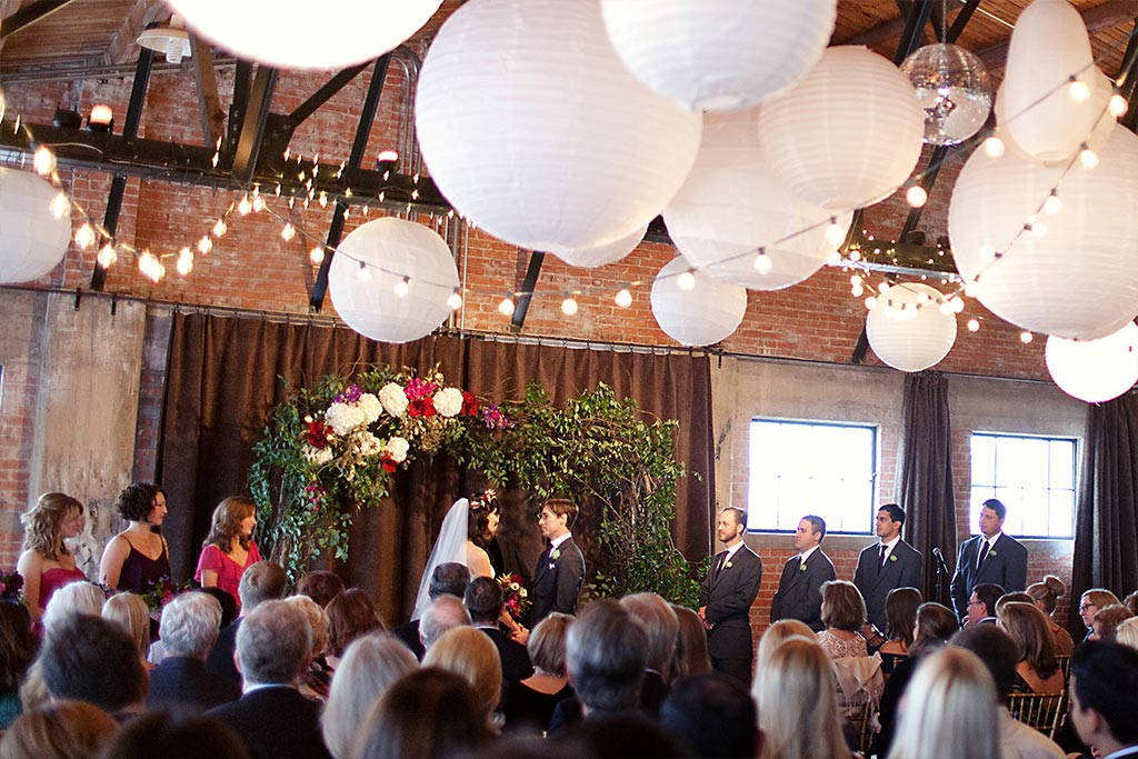 Wedding ceremony with floral and greenery altar at Hickory Street Annex in Dallas