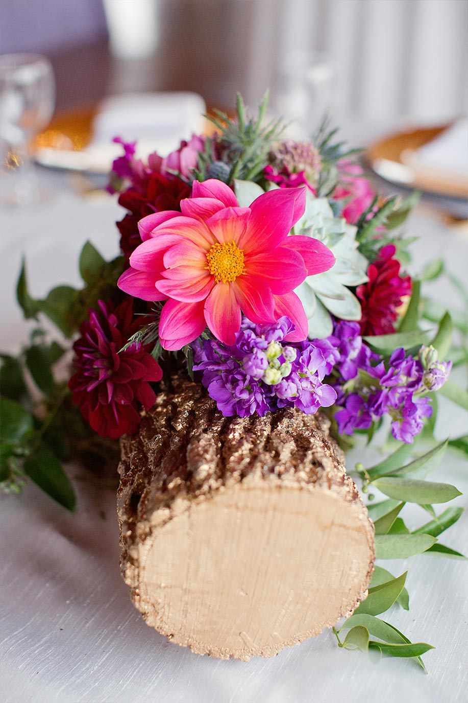 Gold log wedding centerpiece with pink and purple floral