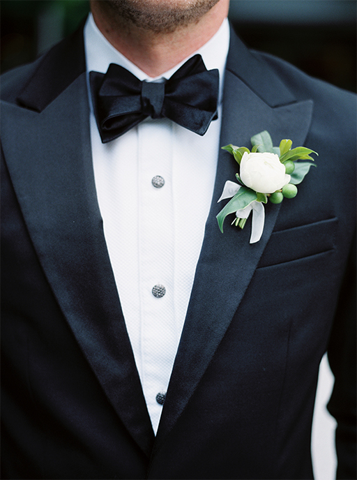 Groom's black tux with bow tie and white boutonniere