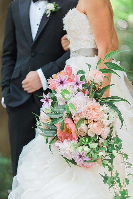 Groom and Bride portrait with cascading pink and peach bouquet