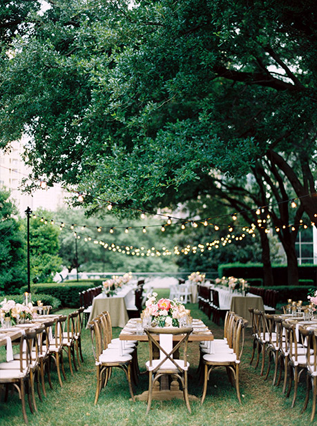 Wedding reception long table and cross back chairs with hanging cafe lights at Marie Gabrielle in Dallas