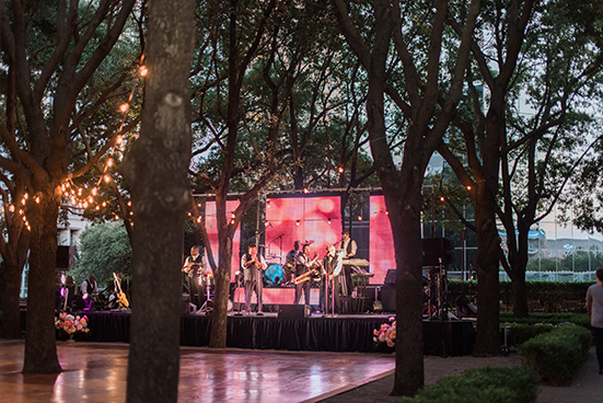 Emerald City Band on stage with outdoor dance floor and cafe lights at wedding reception at Marie Gabrielle in Dallas