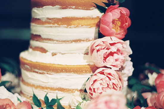 4-tier naked wedding cake detail with smeared buttercream and pink and peach fresh floral by Sugar Bee Sweets
